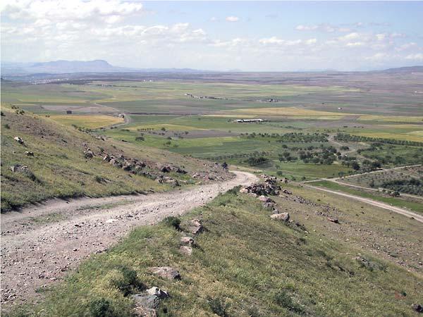 Vanaf de heuvel uitzicht over een uitgestrekte groene vlakte