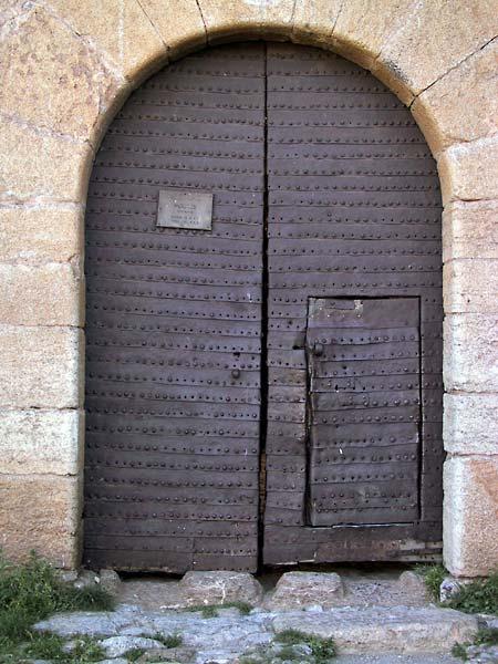Ronde poort met houten deuren vol ijzeren beslag