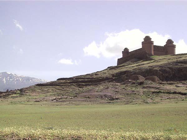 Het kasteel van verderaf met de besneeuwde Sierra Nevada op de achtergrond