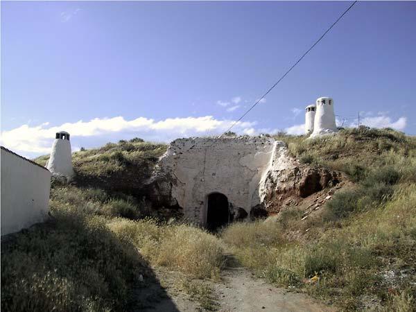 Witte gemetselde ingang naar woning onder heuvel; witte ronde schoorsteentjes er boven