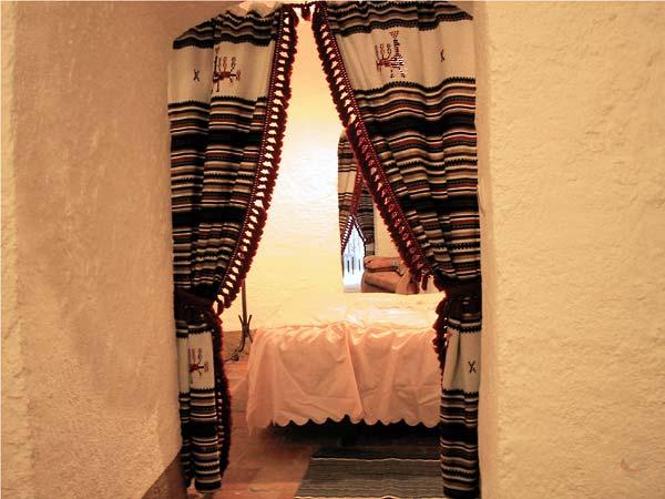 Witte muren, twee geweven gordijnen, met zicht op bed met glanzende roze sprei