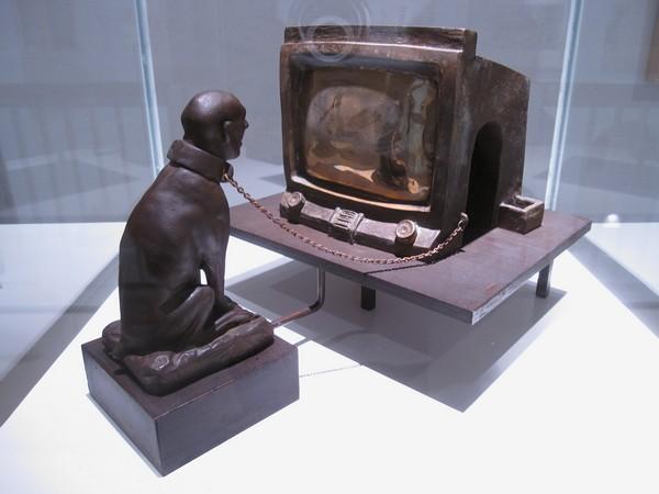 beeld van geketende man achter tv