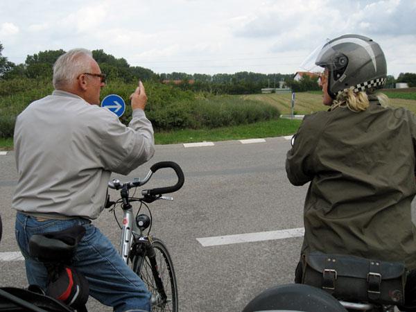 man op fiets wijst de weg aan iemand op een motor