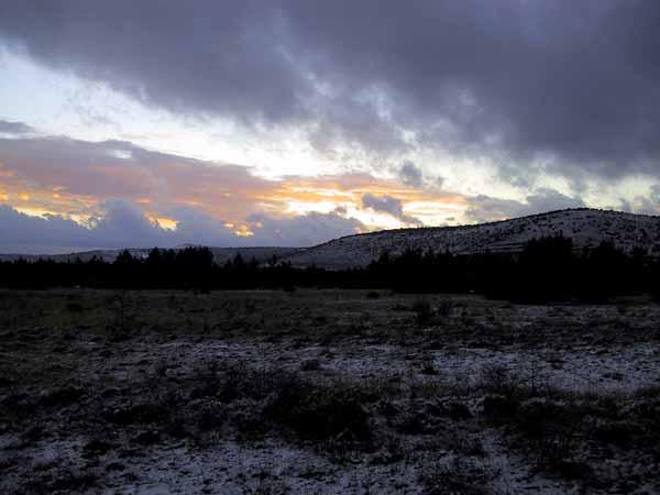 Zonsondergang in besneeuwd landschap