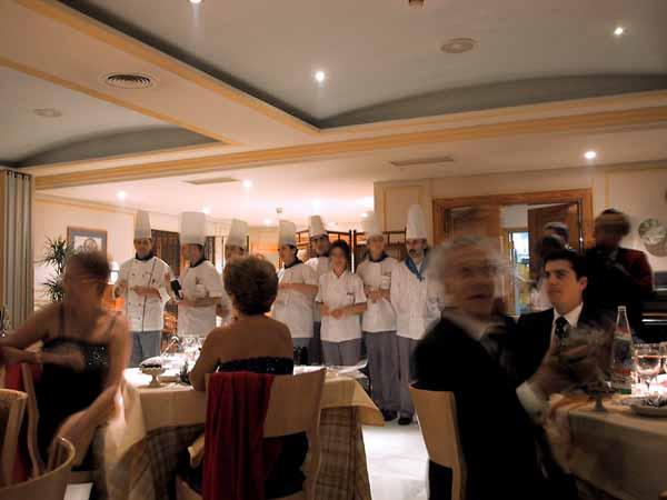 Mensen aan restauranttafeltjes met daar achter de koks op een rij