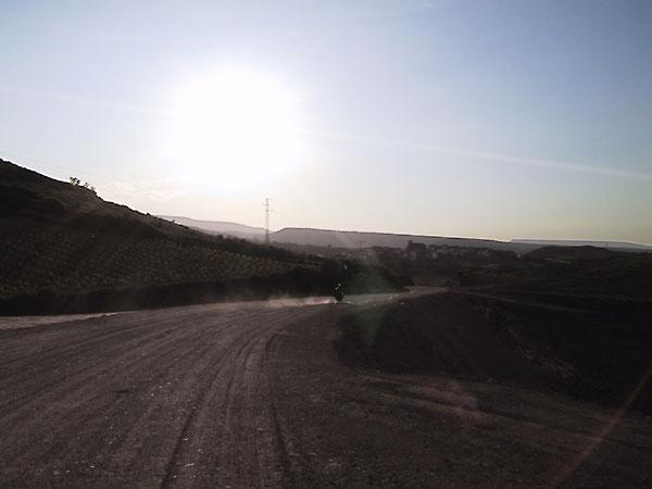 Met de motor over een onverharde weg stuiven