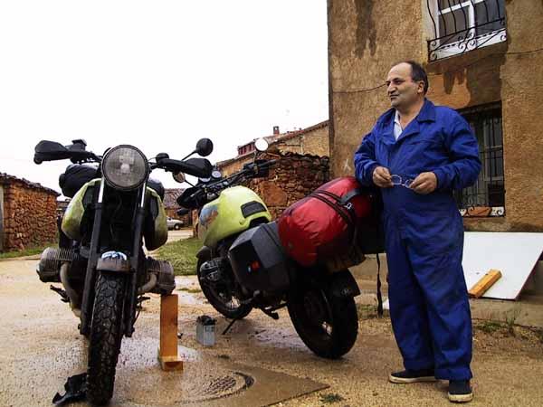 Man staat in de modder naast twee motoren