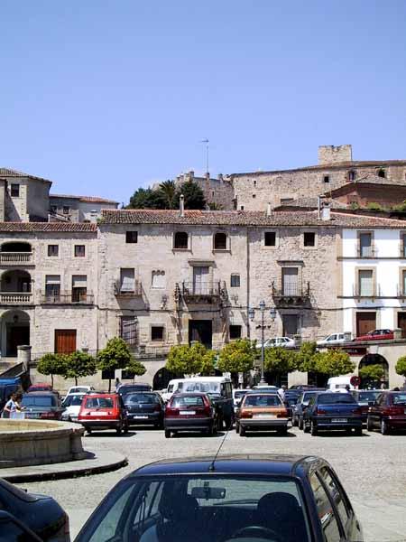 Plein met oude huizen en geparkeerde auto's