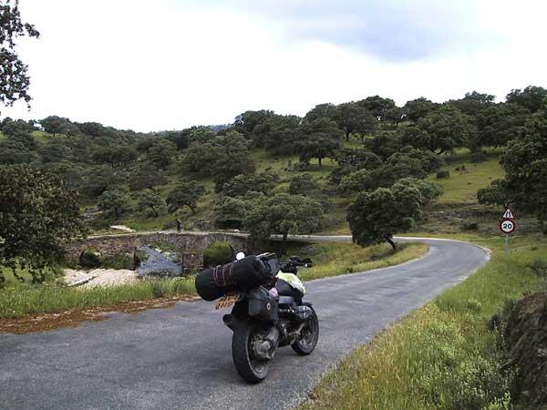 Motor in landschap van gras en olijfbomen, en oude brug